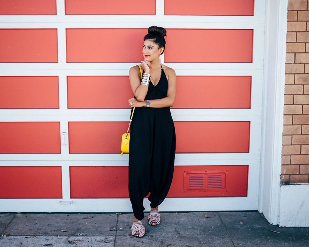 Kelsey Kaplan of Kelsey Kaplan Fashion wearing a pom pom jumpsuit and yellow gucci purse
