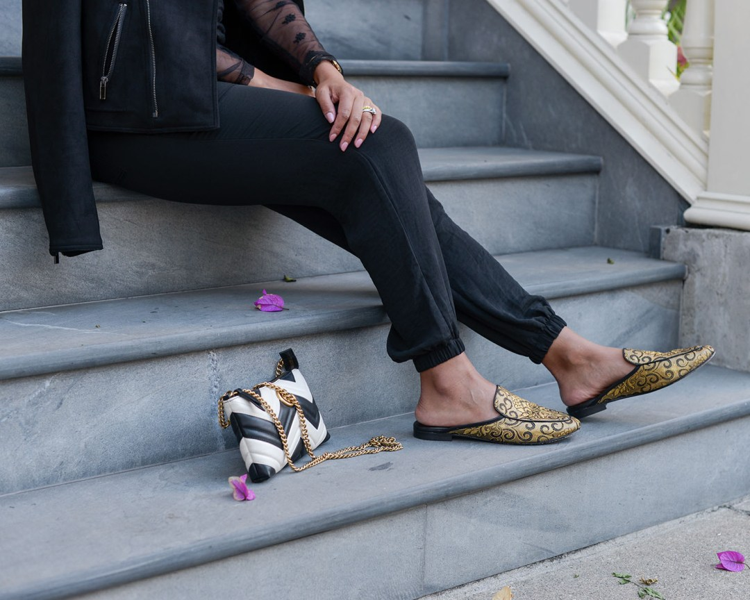 Lifestyle blogger Kelsey Kaplan of Kelsey Kaplan Fashion wearing black joggers and black and gold loafers