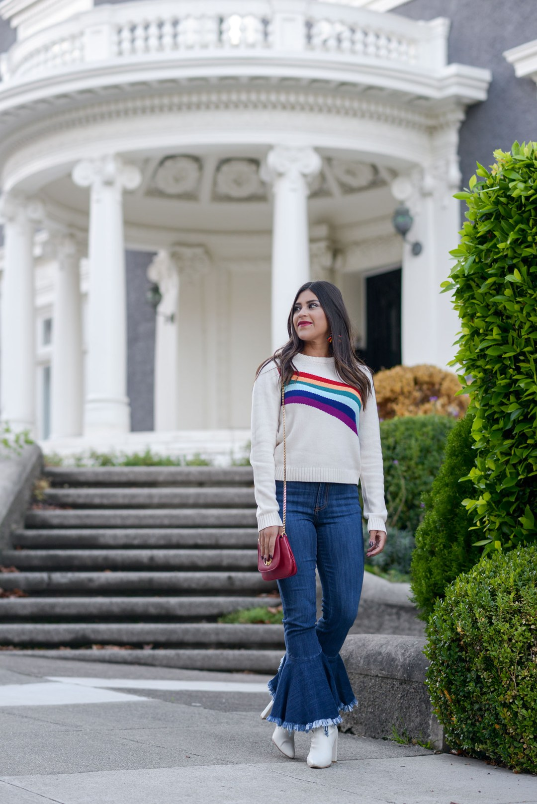 Lifestyle blogger Kelsey Kaplan of Kelsey Kaplan Fashion wearing rainbow graphic sweater and red gucci purse