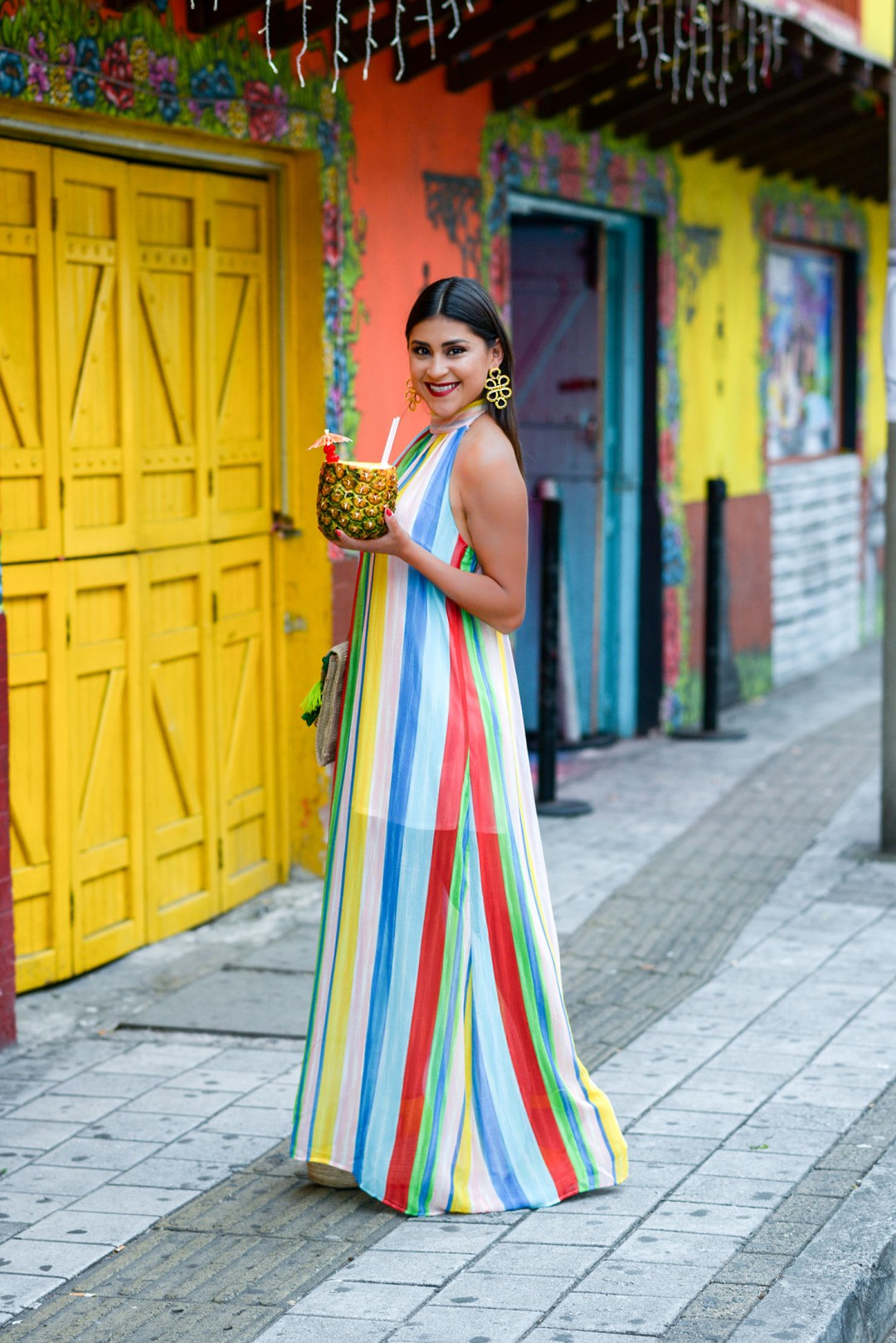 Lifestyle blogger Kelsey Kaplan of Kelsey Kaplan Fashion wearing rainbow maxi dress and straw clutch purse in Medellin