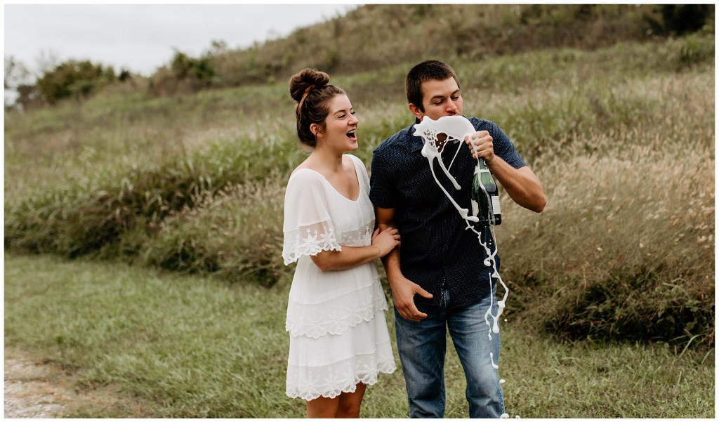 couple celebrating recent proposal with champagne in outdoor tennessee engagement session