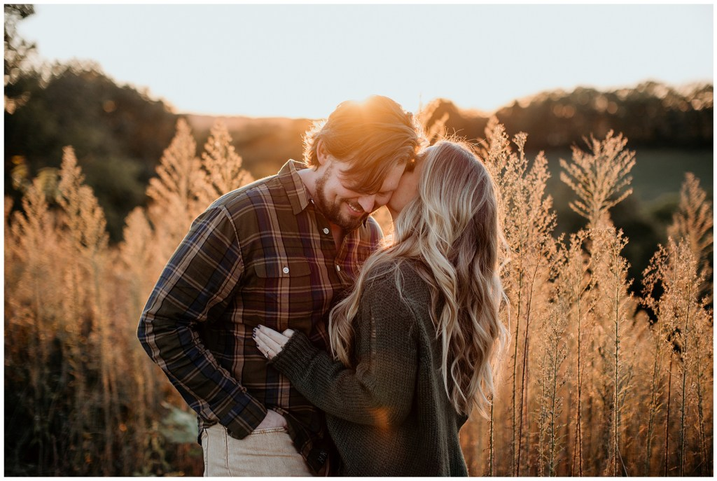 woman whispering in man's ear during engagement session