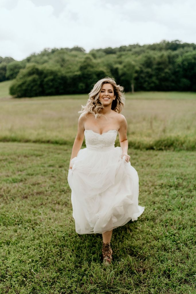 bride running through tennessee field during outdoor wedding