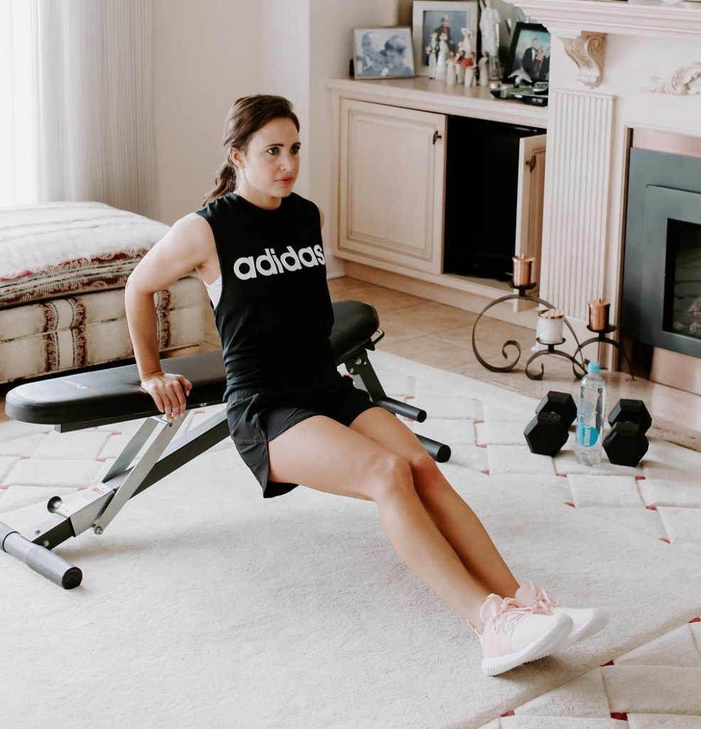 At home arm workout using a bench or chair. Tricep dips at home. No weight workout. Woman wearing adidas top, lululemon running shorts, and pink adidas sneakers.