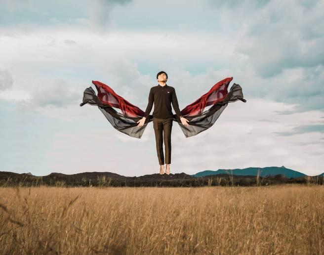 stylish barefoot man levitating above field