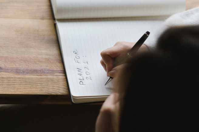 crop faceless woman writing plans in diary