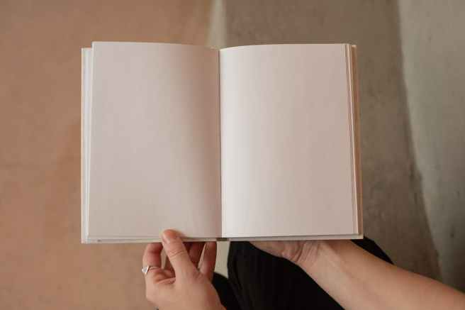 woman holding book with blank pages