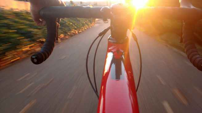 person riding on red road bike during sunset