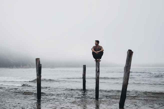 man sitting on wooden pole against foggy sky