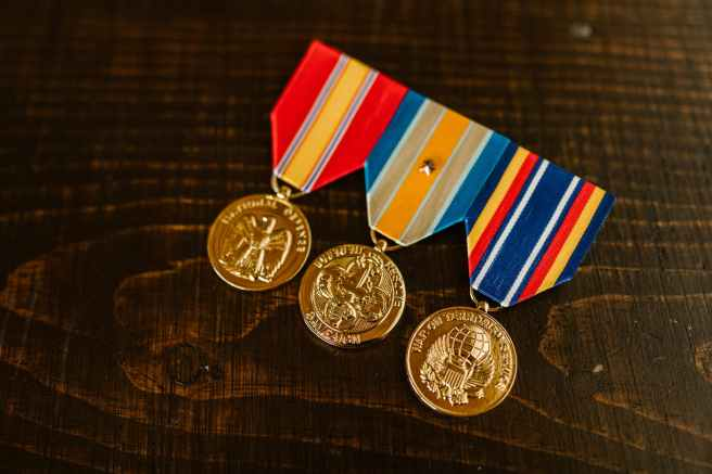 close up photo of medals on wooden surface