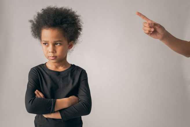 faceless person punishing black girl