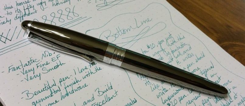 The Nemosine Neutrino Fountain Pen laying on top of the writing sample, which uses Pelikan Edlestein Aquamarine ink