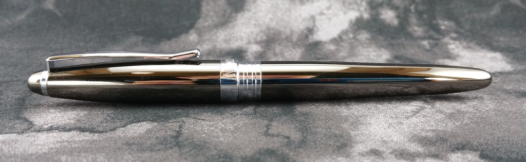 A photo of the Nemosine Neutrino Fountain Pen in gunmetal, capped and laying down