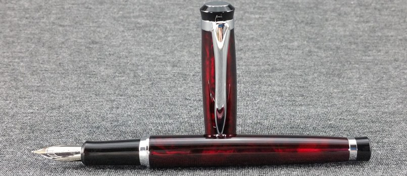 The Baoer 508 Fountain Pen, uncapped, with the pen laying down and the cap standing up behind it