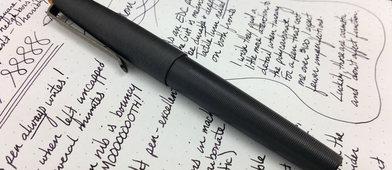 The Tactile Turn Gist Fountain Pen, capped, and laying down on top of the writing sample