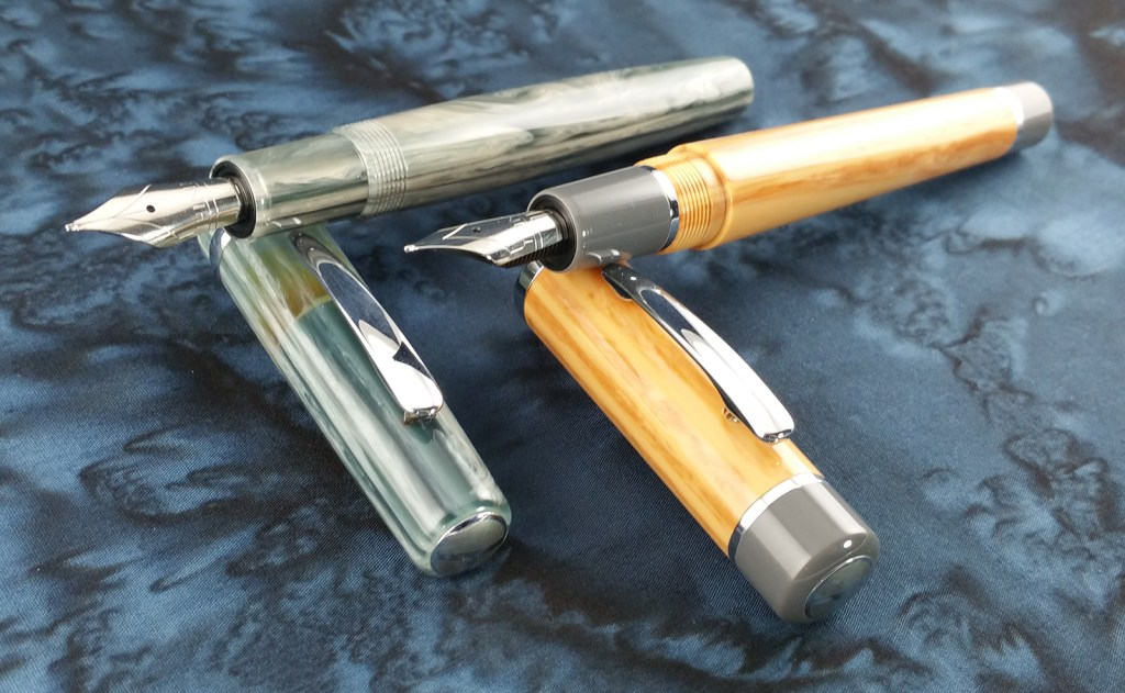 Think Couture Fountain Pens (Vacation and Violino) Uncapped, with the pens laying down on top of their caps