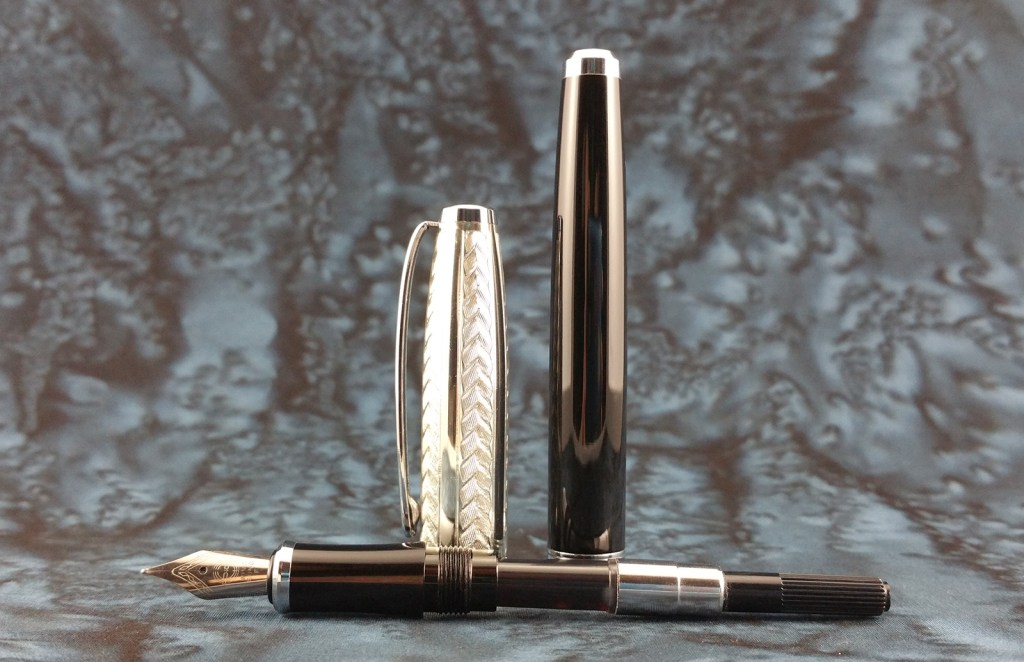The Yongsheng 088 Fountain Pen, disassembled, with the nib unit and converter laying down and the cap and barrel standing up behind them