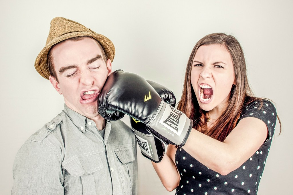 Woman in boxing gloves punching a man...OUTRAGE!