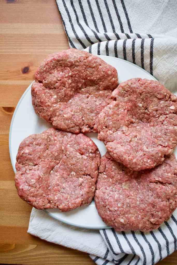 Seasoned hamburger patties waiting to hit the grill