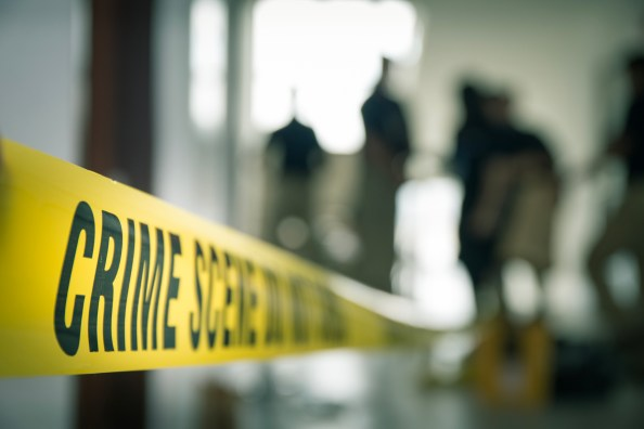 crime scene tape with blurred forensic in cinematic tone