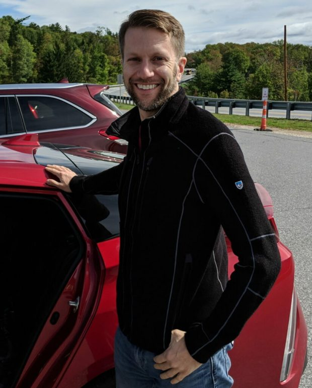Portrait profile photo of smiling, bearded man standing next to red car