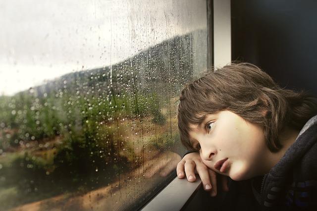 雨で憂うつな少年
