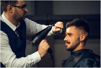 剛毛の男性が髪型をセットしてもらっている