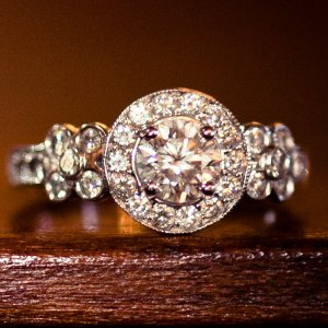 Custom designed wedding ring, with round cut center diamond, band with 32 surrounding diamonds