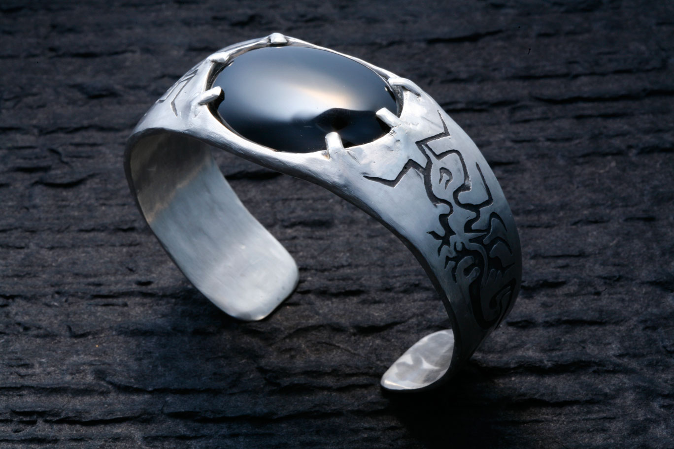 Custom made sterling silver cuff, with a fire ant etching and a centered onyx cabachon