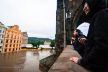 People near Prague bridge watching the flood