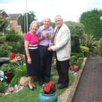 Couple standing in developed garden with Chairman of Parish Council