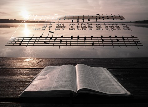 Open Bible and hymn near an ocean at sunset