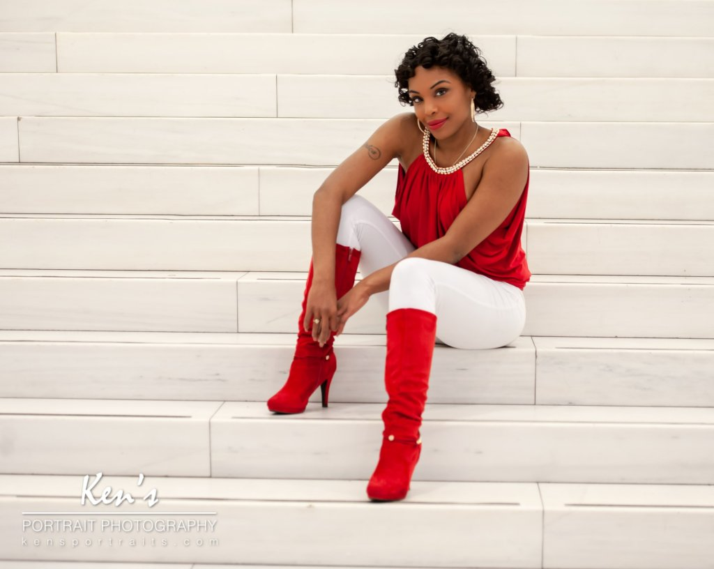 Setting the Trend by Kens Portrait Photography. Maribel sits on the steps in the Oculus located in New York City. Her red shirt and red boots contrast perfectly with the white marble steps. It is no wonder that the Fashion Tag Blog considers red boots to be one of the hottest fashion trends of 2018.  The Fashion Portrait Experience at Ken's PortraitPhotography includes an initial consultation, two hours of in studio or on-location photography, and a personalized image review session. You can fulfillyour fashion dreams by adding professional hair andmakeup artistryto the fashion portrait experience.  The studio for Ken's PortraitPhotography is located right on the southwest corner of West Capital Park in Albany, NY. In addition to what can be created in the studio, this historic and architecturally rich area provides beautifulbackdrops for professional portraits, couple portraits, senior portraits, family portraits, engagement portraits, and wedding portraits.