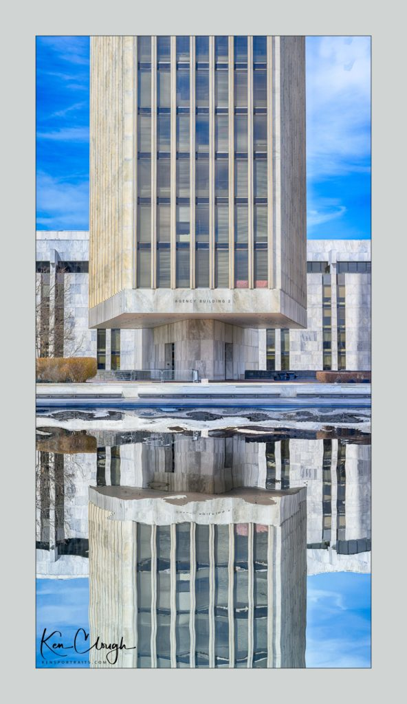 Empire State Plaza by Kens Portrait Photography. This past Sunday was a beautiful sunny day. I just had to get out of the studio and take a walk around the neighborhood. I am so fortunate that my studio is located right on the southwest corner of West Capital Park in Albany, NY.  In addition to what can be created in the studio, this historic and architecturally rich area provides beautiful backdrops for acting headshots, professional portraits, couple portraits, senior portraits, family portraits, engagement portraits, and wedding portraits. The original image of Agency Building 2 at the Empire State Plaza was a good image but at this time of year, the reflecting pool is empty. Just a week or two ago the ice skating rink was there and frozen over. You can see the original and unedited image below. I looked at the image and just thought that it would look so much better if it had been later in the season and you could see a reflection of the building. Not to be deterred, I used a little photoshop processing to add the water back in the reflecting pool. At Ken's Portrait Photography we use the same care in all of the images we take. Whether it is capturing an image for acting headshots, professional portraits, couple portraits, senior portraits, family portraits, engagement portraits, and wedding portraits, we want you to look your best.