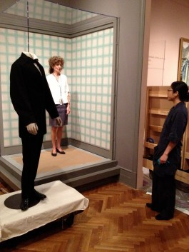 The curator of the exhibition, Gloria Groom, indicates the position where wants the suit placed.