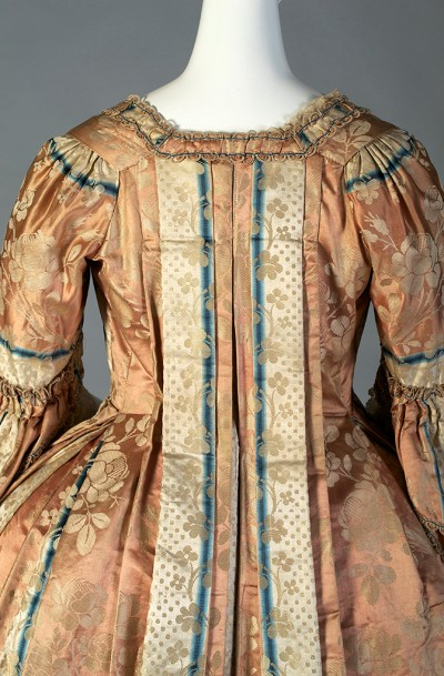 The textile is laid out so the stripes fall down along the center of the Watteau folds.