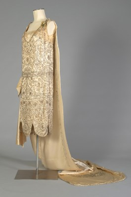 Three quarter front view of silk satin wedding dress shown with the train, KSUM 1983.1.334.