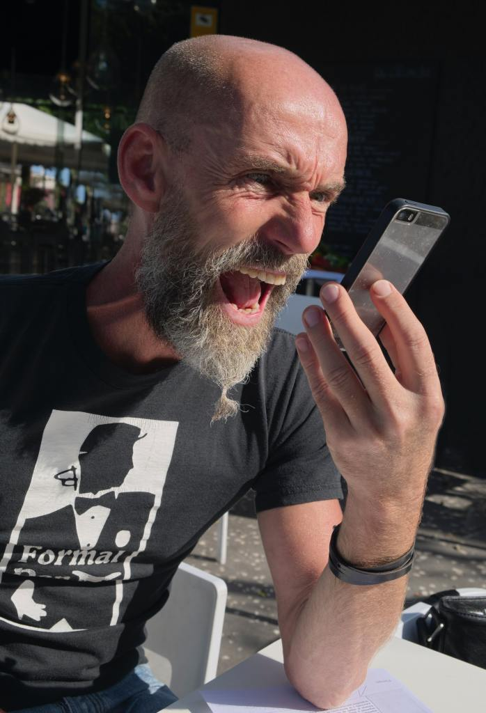 A Bearded man in a black shirt screaming angrily at his phone