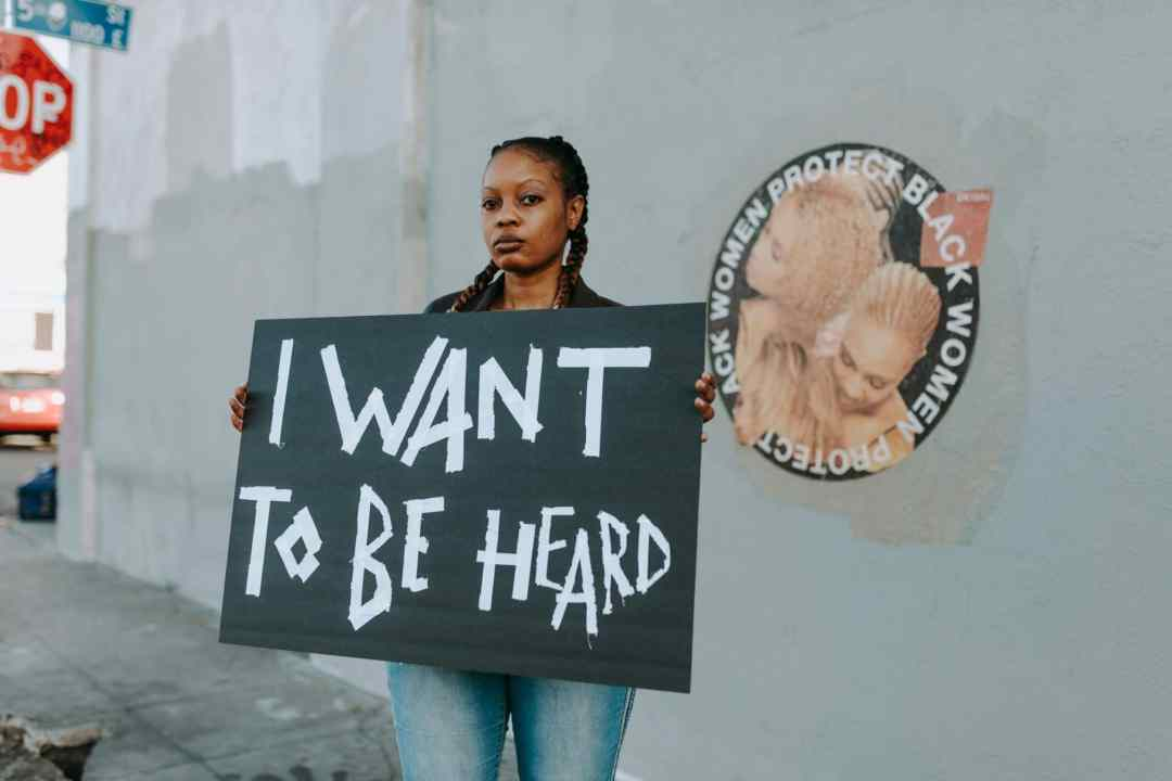 black woman with anti-racism poster