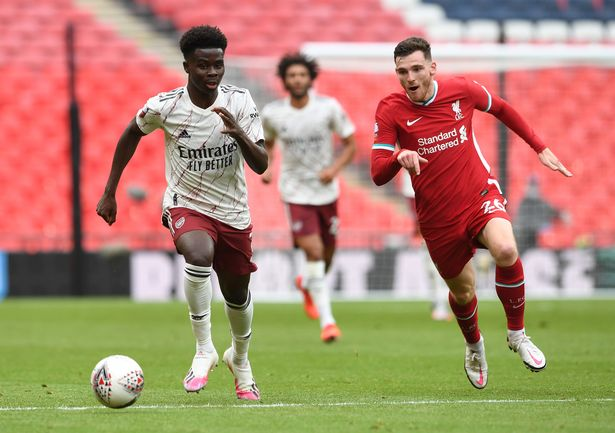 Bukayo Saka of Arsenal takes on Andrew Robertson