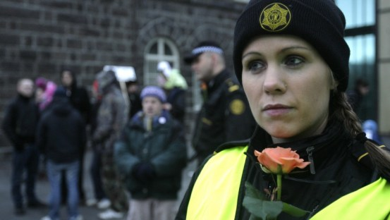 An Icelandic police officer stands guard at a peaceful protest near Iceland's Parliament house in Reykjavik. | Credit: Ints Kalnins/Reuters