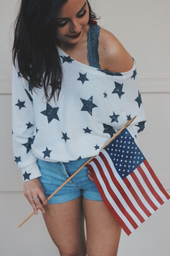 Girl wearing 4th of July attire while holding an American flag