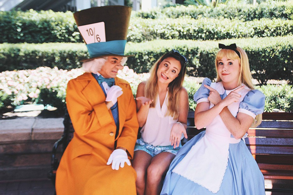 A girl making silly faces with Alice and the Mad Hatter