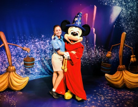 Character attendant with Mickey Mouse in his Sorcerer outift