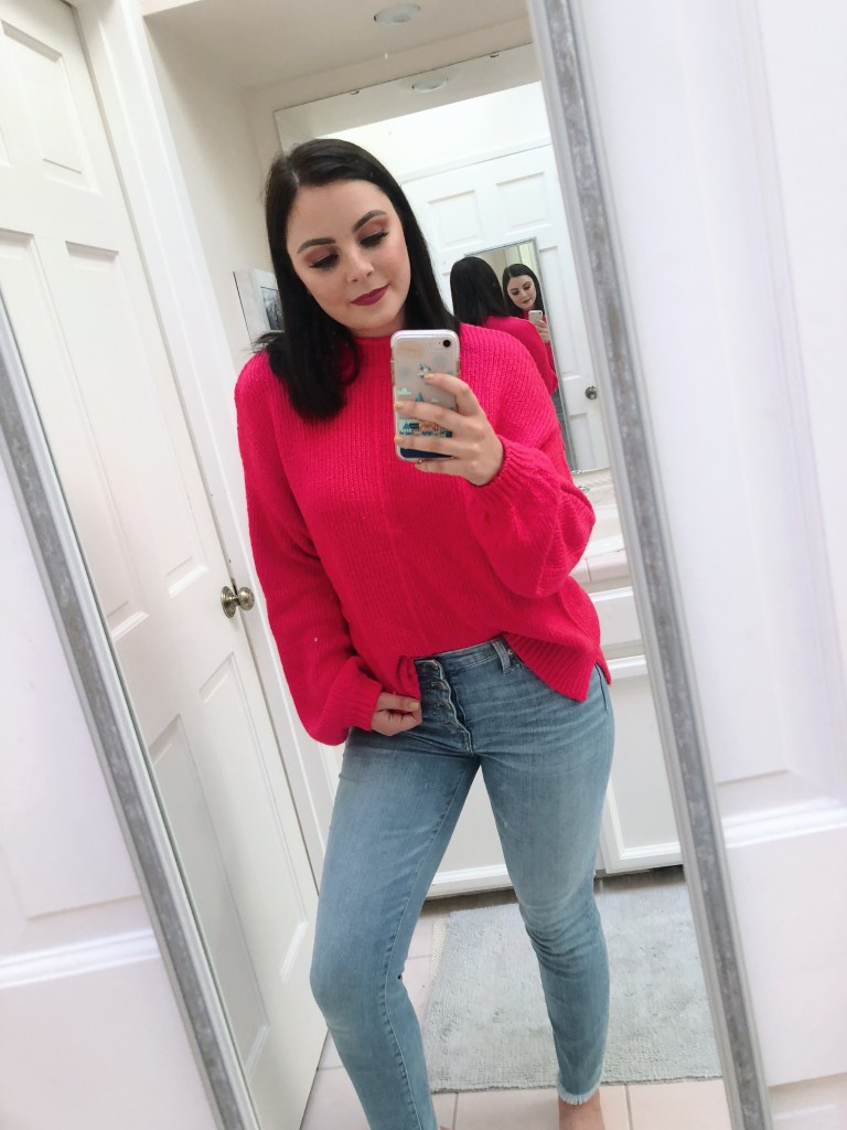 Hot pink balloon sleeve sweater with light wash blue jeans