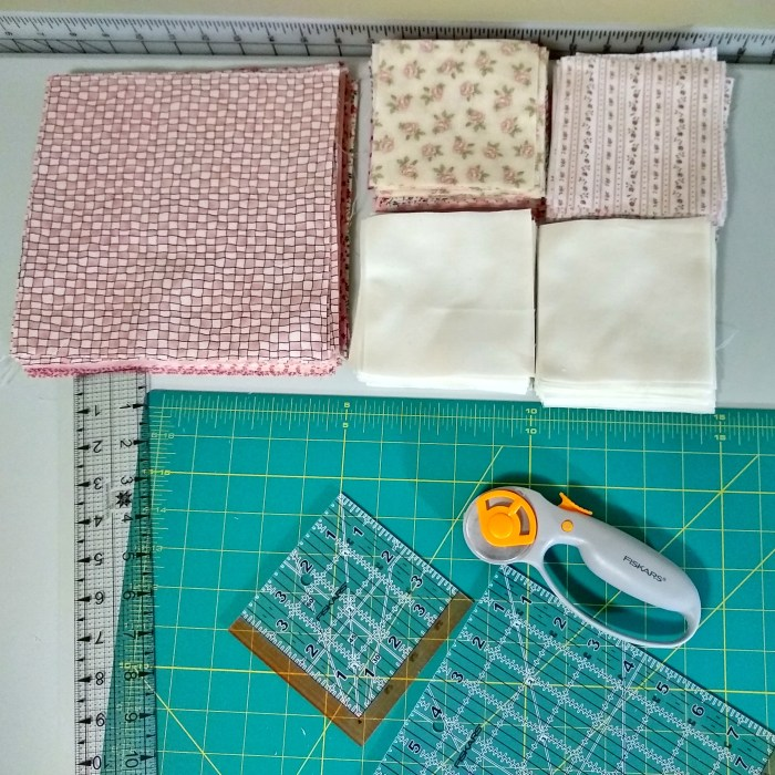 A quilter's workspace including large and small squares of quilt fabric, a rotary cutter, acrylic rulers, and cutting mat.