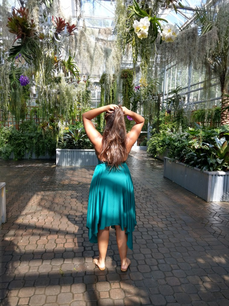 Keri Elaine beautiful woman at the Atlanta Botanical Gardens emerald green a-line dress and the curious garden exhibit. Long healthy brown hair