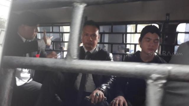 Abdul Qadir Jaelani alias Dul menemani ayahnya, Ahmad Dhani masuk ke mobil tahanan. (Ismail/Suara.com)