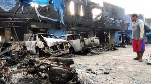 Seorang warga mengamati Kantor Bea Cukai Papua serta sejumlah mobil yang terbakar saat berlangsungnya aksi unjuk rasa di Jayapura, Papua, Jumat (30/8/2019). [ANTARA FOTO/Indrayadi]