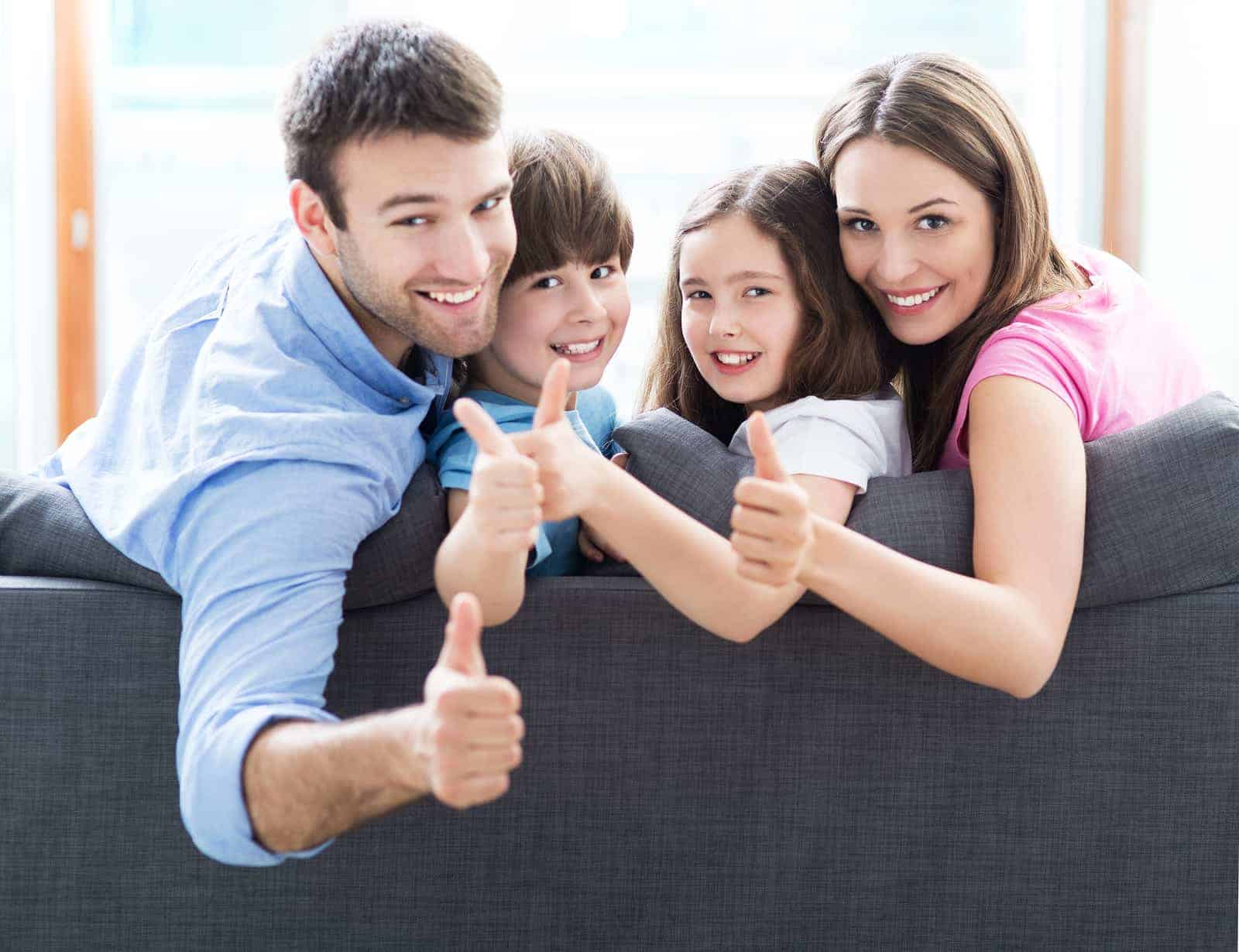 Family at home with thumbs up
